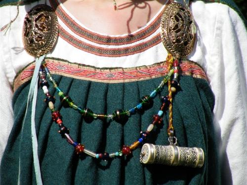 Detalle de la vestimenta de una vikinga; podemos observar los detalles, los objetos, y las cadenas.